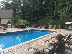 Fully landscaped in ground pool with loungers for guests.