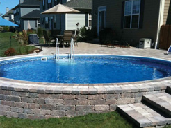 Round semi in-ground pool with custom stonework exterior walls and matching steps/patio.