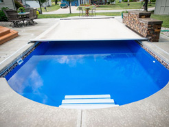 Retractable Swimming Pool Cover shown on an in ground pool.